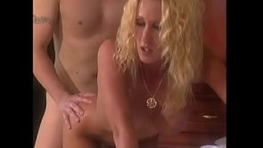 Guy fucks a curly-haired blonde with big boobs on white sheets of doggy style